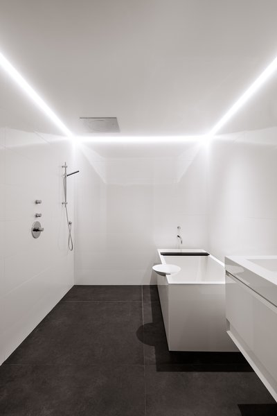 The guest bath, located in the lower level of the house, has a tub by Wetstyle. LED lights are recessed in a channel along the drywall ceiling.