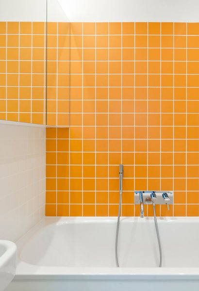Bath time is never dull for the couple's two young children, thanks to bright orange Interni tiles by Domus.