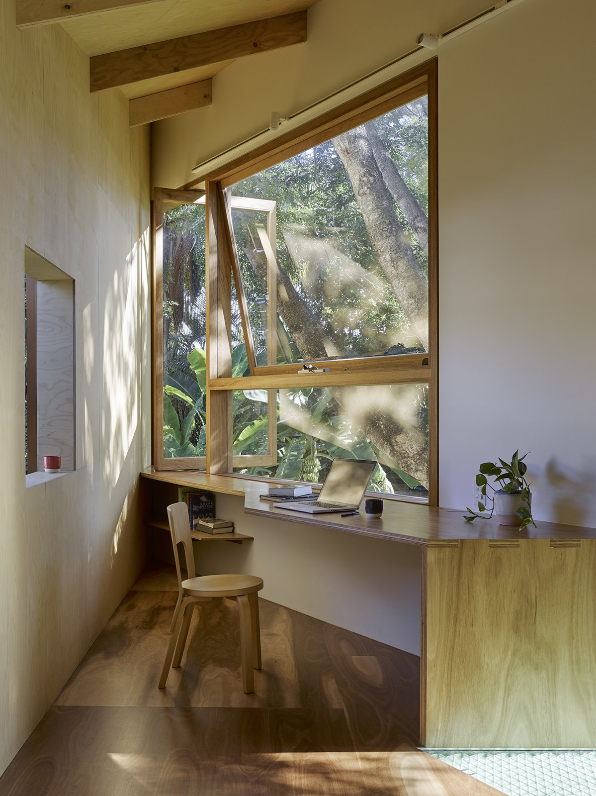 Office, Medium Hardwood Floor, Chair, and Desk A small workspace overlooks the gardens.  Photo 6 of 11 in This Triangular Tree House Adds Whimsy to a Backyard in Australia