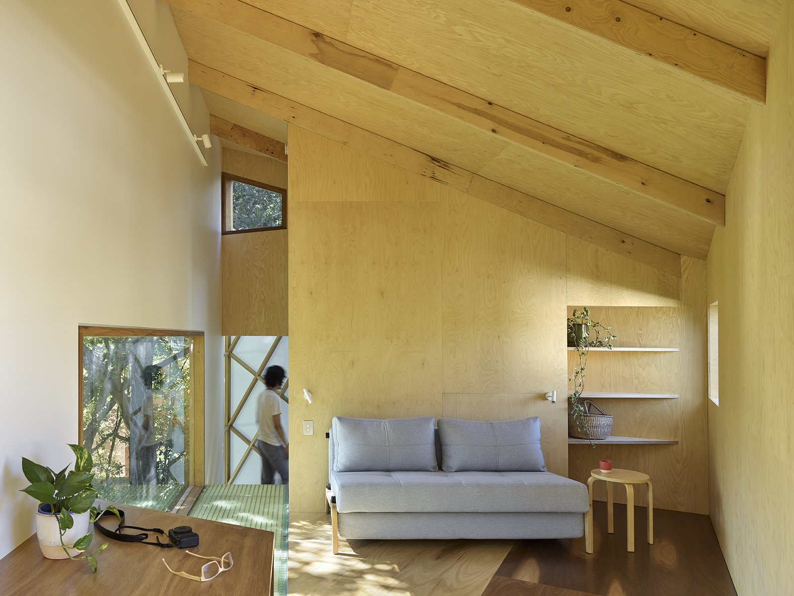 Living Room, End Tables, Sofa, Wall Lighting, Shelves, Track Lighting, and Medium Hardwood Floor The interior of the tree house is made up of a set of informal spaces, including a loft on the top floor.  Photo 7 of 11 in This Triangular Tree House Adds Whimsy to a Backyard in Australia