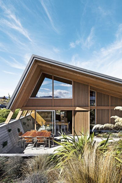 On a scenic but exposed lakefront site on New Zealand's South Island, architects Tim Lovell and Ana O'Connell of Lo'CA created a pitch-roofed 2,690-square-foot residence for Tim's parents. The home's courtyard was excavated to help shelter it from high winds. A 10-foot eave over the windows and doors assists with sun shade and heat retention during the intense summer and winter months.