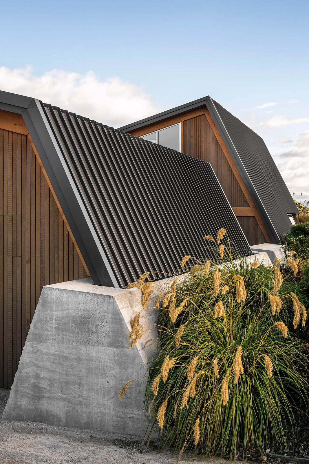 Outdoor, Shrubs, and Retaining Fences, Wall The retaining wall anchors the standing-seam steel roof.  Best Photos from This Bunker-Like Home in New Zealand Fights Back Against Howling Winds Off Lake Wanaka