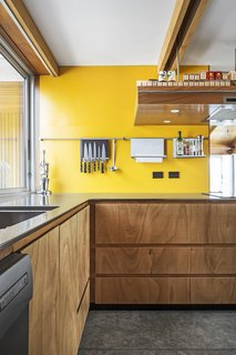 Many of the gaboon plywood cabinets are push-click. The accent wall is painted Fuel Yellow by Resene.