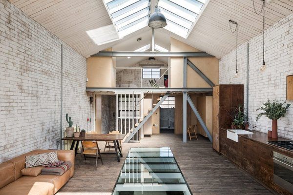 Built as a warehouse, this 2,200-square-foot, one-bedroom home in East London kept its original layout, but now has an open bedroom on the mezzanine level.