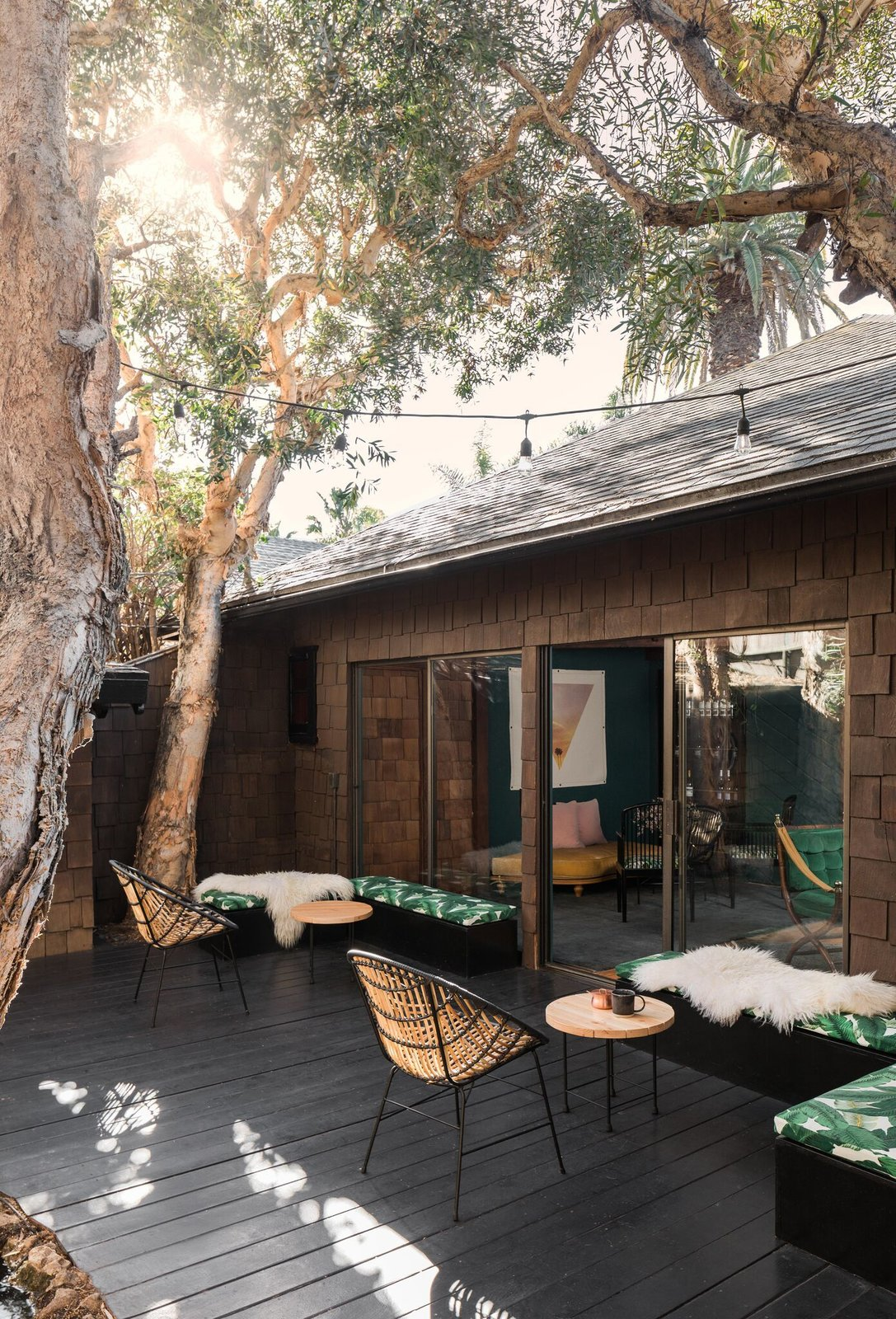Outdoor, Wood Patio, Porch, Deck, Trees, and Side Yard The private patio can accommodate work or play.  Photo 4 of 8 in A 1940s Beach Home Is Restored Into a Gorgeous Clubhouse in L.A.