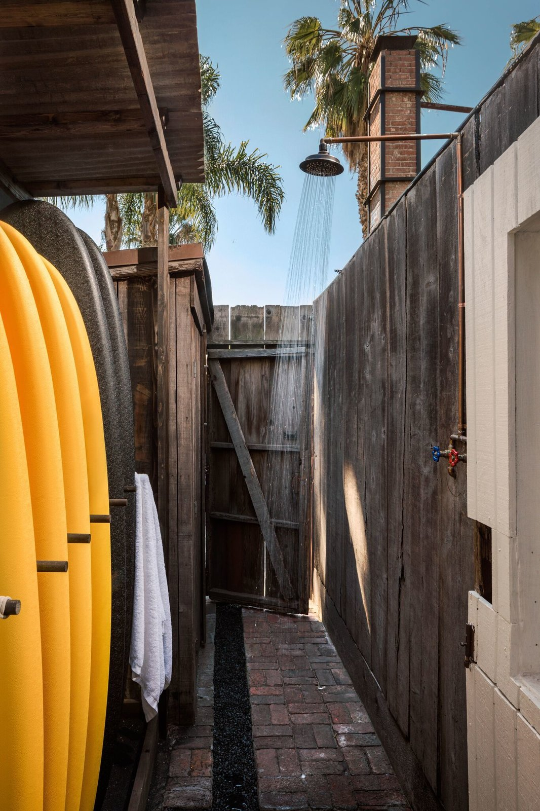 """Outdoor, Side Yard, Wood, and Shower """"I want the members to feel completely comfortable and not want to leave,  Outdoor Shower Wood Side Yard Photos from A 1940s Beach Home Is Restored Into a Gorgeous Clubhouse in L.A."""