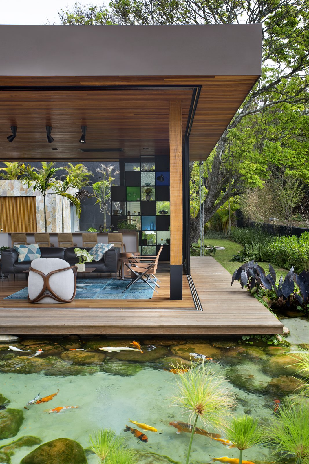 Outdoor, Wood, Back Yard, Small, Horizontal, Trees, Grass, Shrubs, and Boulders The home appears to float above the natural pool, adding an element of whimsy.  Best Outdoor Shrubs Small Photos from This Breezy Brazilian Home Oozes Tropical Vibes