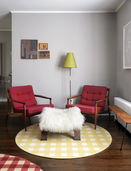"""Over the last decade, architect Francine Monaco and her husband, David Bauer, have filled their bungalow on Long Island with rare furniture, art, and antiques. In the living room, midcentury Danish chairs join a camel saddle covered with an alpaca hide, used as an ottoman. Francine had round """"lily pads"""" cut from gingham-patterned carpeting."""