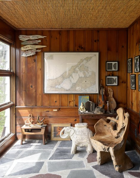 """The sunroom—or """"museum of natural history,"""" as the couple call it—showcases an array of objects, including a massive chair carved from a single tree trunk and a terra cotta elephant used as a side table."""