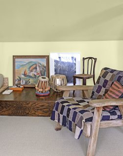 An Adirondack-style chair covered in a vintage quilt sits in one corner.