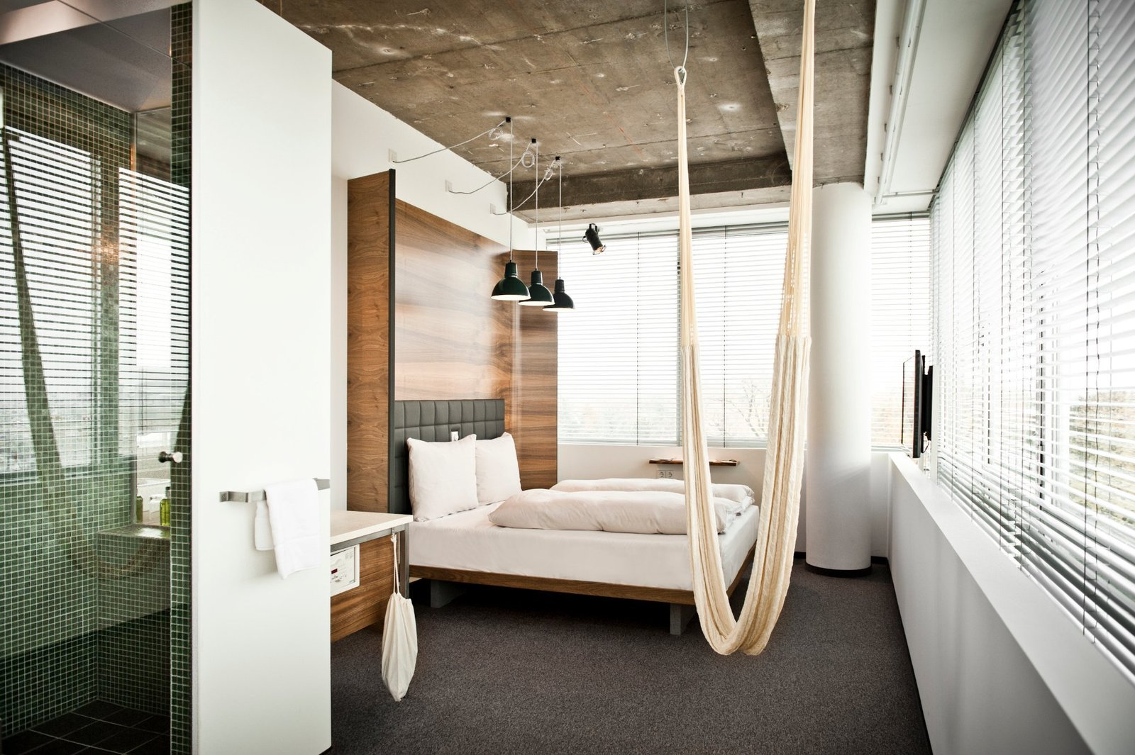 Bedroom, Carpet Floor, Bed, and Pendant Lighting There are no closets and no minibars in the guest rooms, reflecting the designers' minimalist approach. Features include a curved wooden headboard and a hammock hanging from the ceiling. Unfinished ceilings reveal partitions of the old structure, even down to the screws.  Photo 1 of 6 in A Modern Design Hotel in Vienna