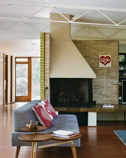 The brick walls extend indoors, where Girard used a hearth to  organize the living area, presaging his and Eero Saarinen's revolutionary concept for the conversation  pit at the Miller House.