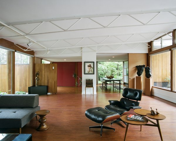 In the living room, the slanted, open-joist ceiling rises to almost 10 ½ feet. A fusuma door leads  to the dining room. The torso sculptures are by Janice Trimpe.