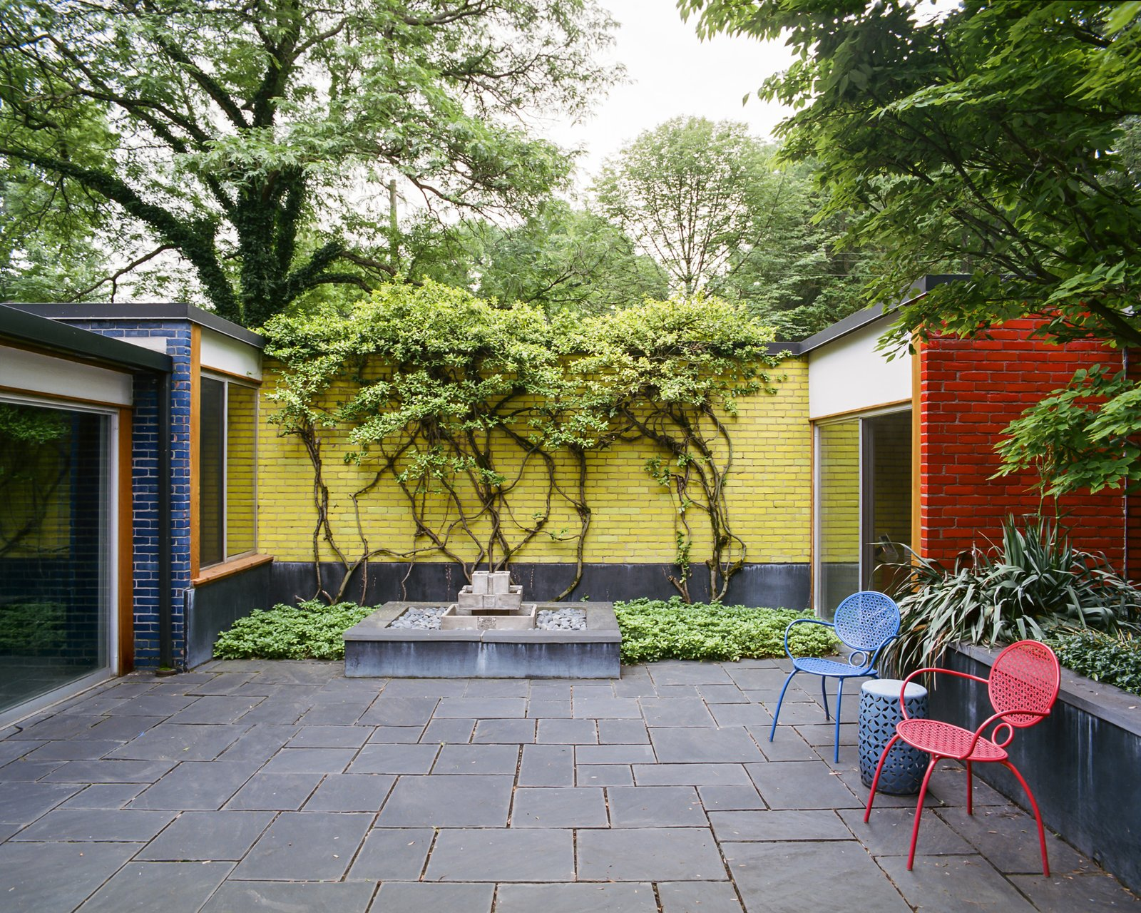Outdoor, Stone, Garden, and Small Vines spill over primary-colored, glazed-brick walls, which recall Girard's eye-popping graphics.  Best Outdoor Garden Photos from This Michigan Couple Found Out They Own the Last Standing Home by Alexander Girard