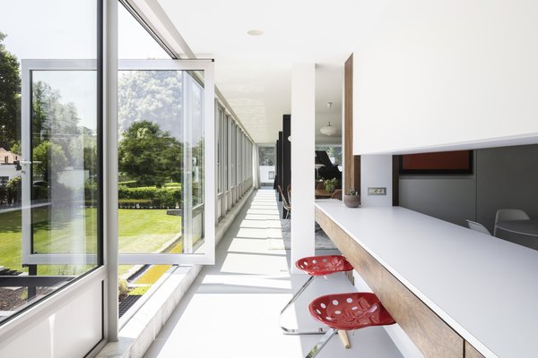 A pivoting glass door leads from the second-story kitchen to an elevated terrace and onto the lawn. The Mezzadro stools are by Achille and Pier Giacomo Castiglioni.
