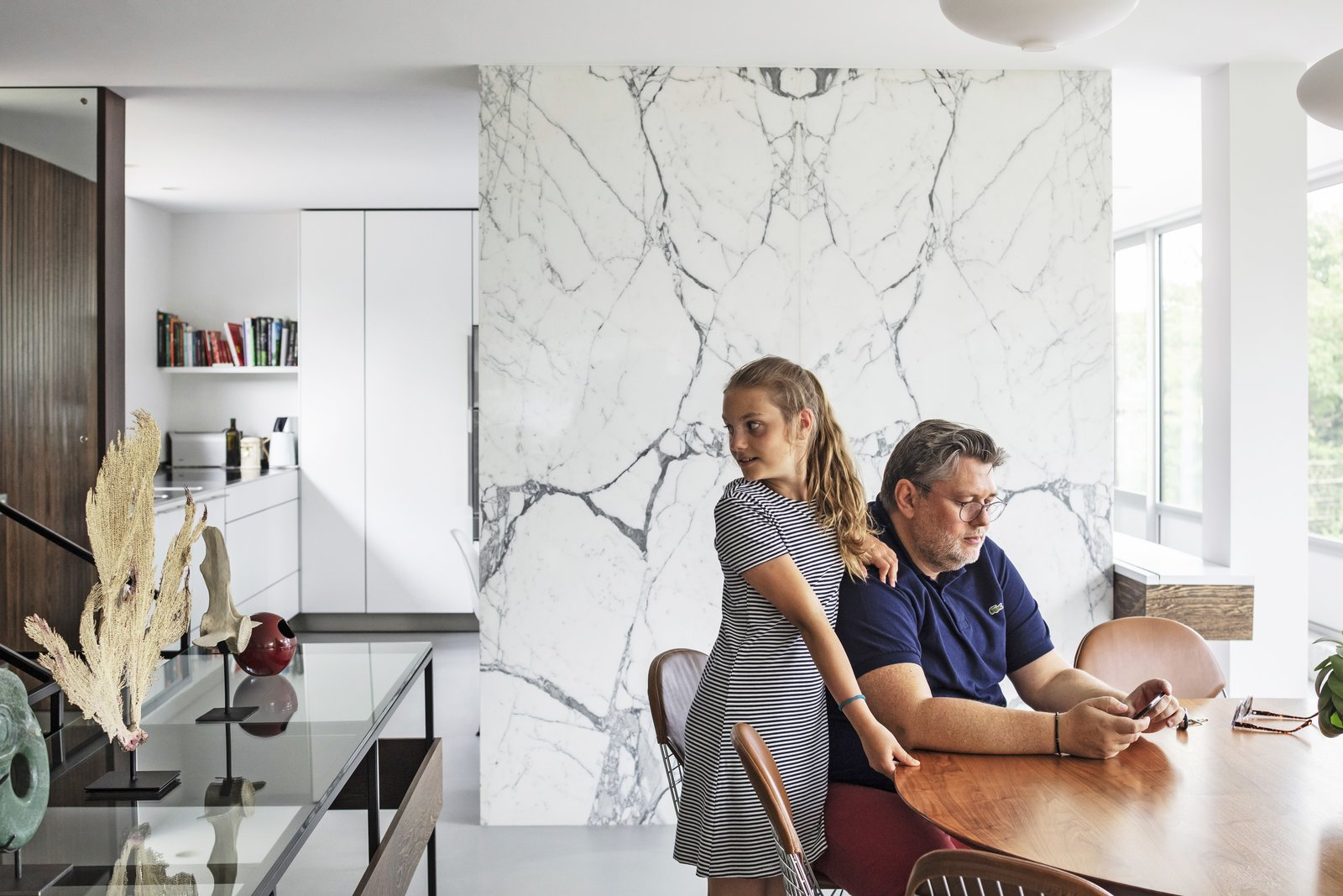 Dining Room, Chair, Table, and Pendant Lighting Resident Simon Mason, joined by his daughter, sits on a leather-upholstered Bertoia side chair.  Best Photos from A Major Restoration Updated This Midcentury Landmark in Belgium