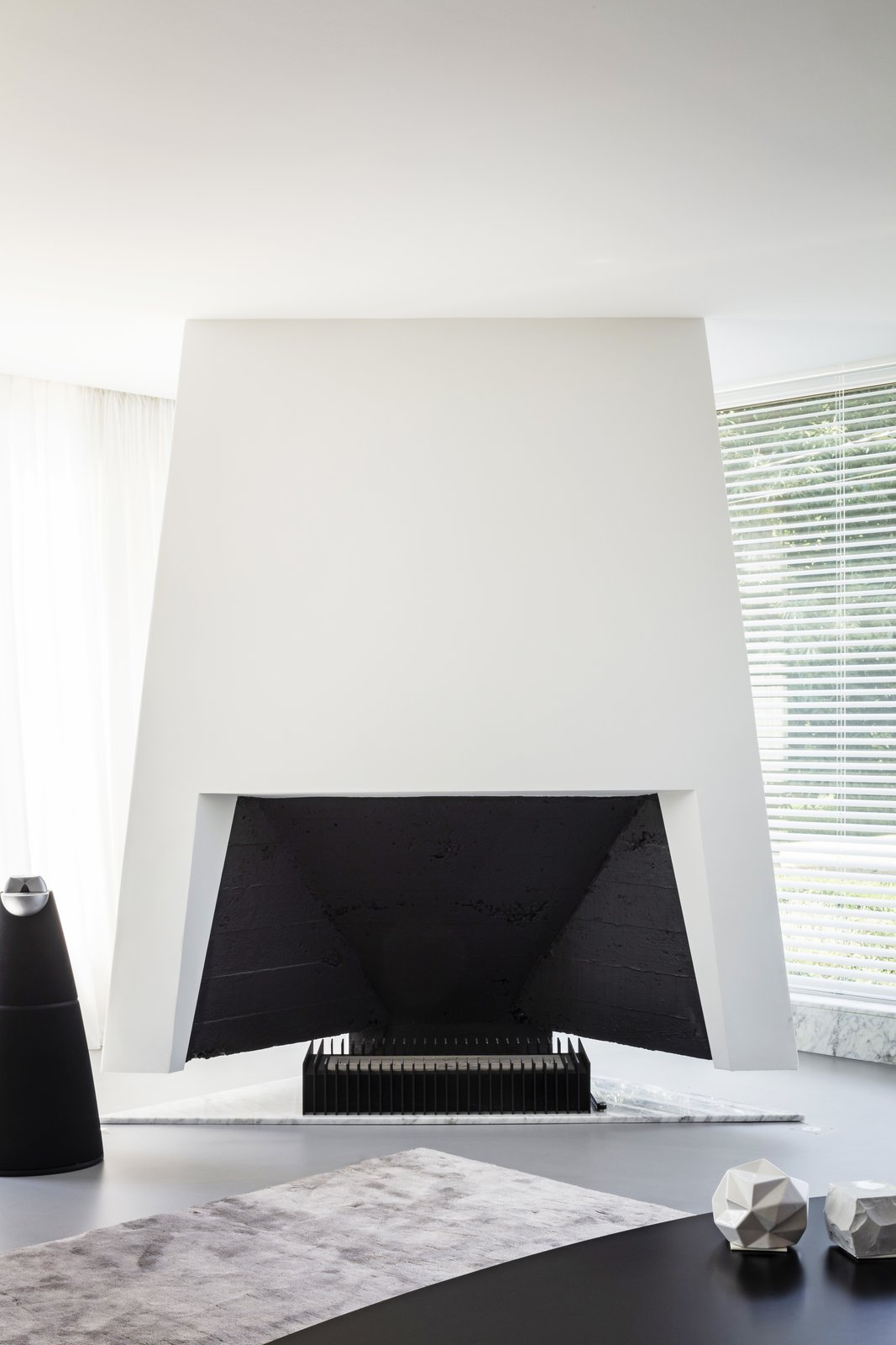 Living Room, Corner Fireplace, and Rug Floor The futuristic fireplace, designed by Engels, is flanked by a BeoLab 20 speaker by Bang & Olufsen.  Best Photos from A Major Restoration Updated This Midcentury Landmark in Belgium