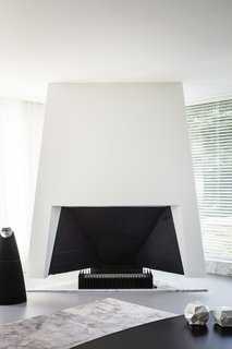 The futuristic fireplace, designed by Engels, is flanked by a BeoLab 20 speaker by Bang & Olufsen.