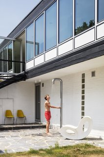 A Voido rocker by Ron Arad for Magis sits by the outdoor shower, also new.
