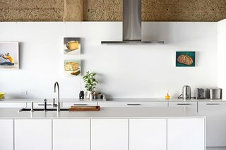 The kitchen features SieMatic cabinetry, Neolith countertops, and a faucet by Dornbracht. Mike Geno's paintings of bread and cheese hang near a Lee Materazzi photograph.