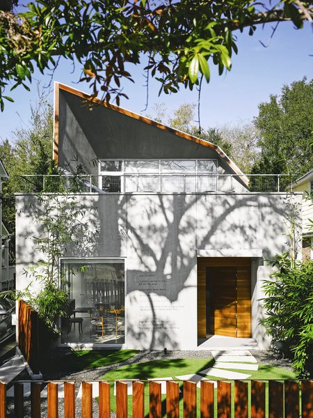 "The transformation of  a 1950s eyesore into an elegant, gallery-like home was a creative challenge for architect Kevan Hoertdoerfer and all involved. The poem ""Roll the Dice"" by Charles Bukowski is painted on the facade. ""It expresses how we  felt about the project,"" says resident Karen Baldwin. ""Everybody  roll with it—everybody do their thing."""