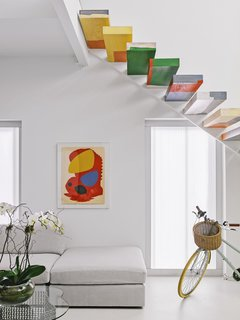 A floating wood staircase hand-painted by artist Tess Thomas  adds more than a pop of color.