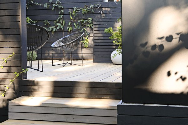 The cedar decks were left to bleach in the sun for one summer and then finished with a light gray wash. Metal Solair chairs are in keeping with the tricolor palette of black, white, and green.