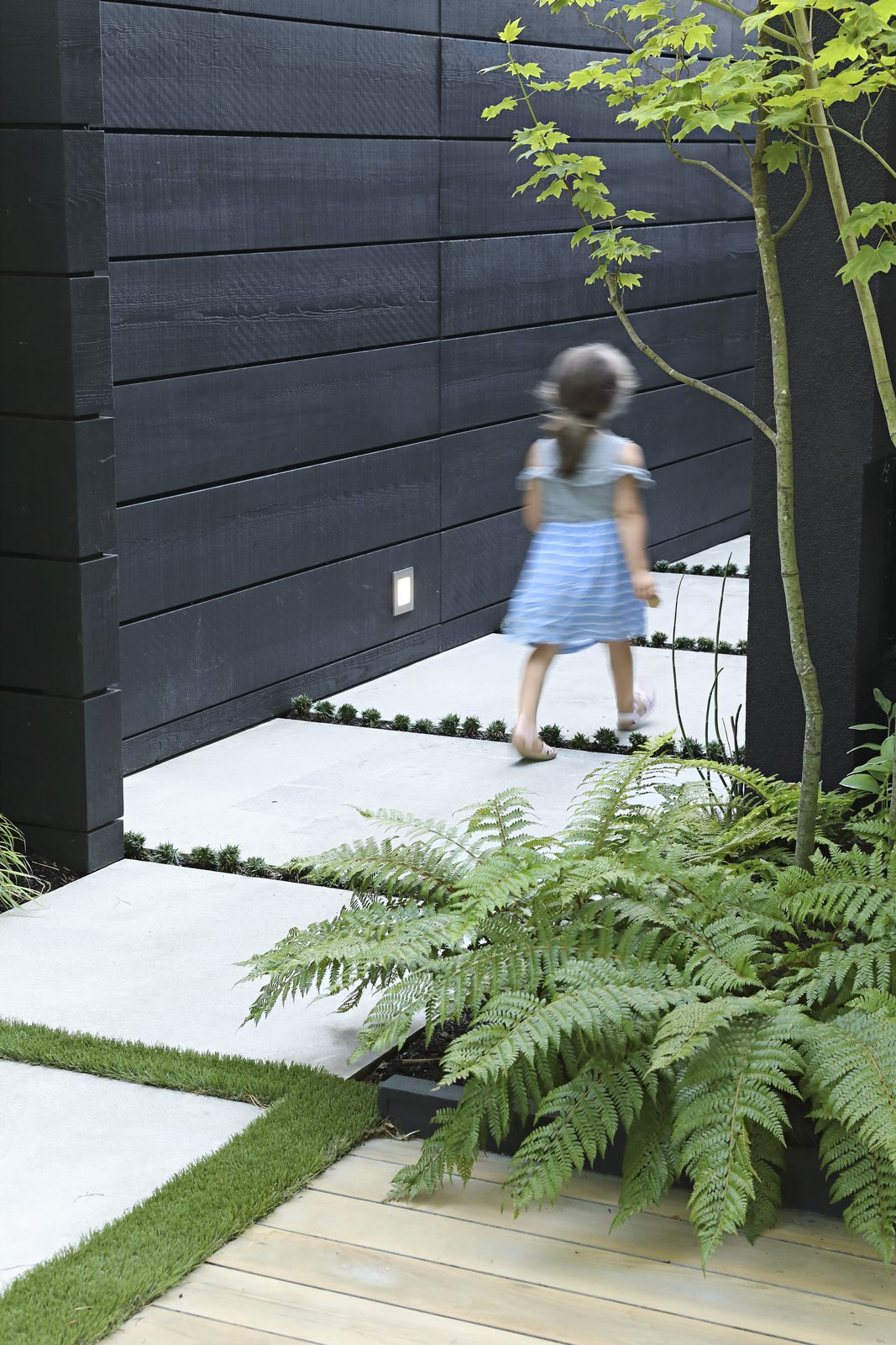Outdoor, Wood Fences, Wall, Horizontal Fences, Wall, Concrete Patio, Porch, Deck, Side Yard, Trees, and Shrubs Hana Bea, 6, follows the concrete pavers that lead from the front yard to the side entrance.