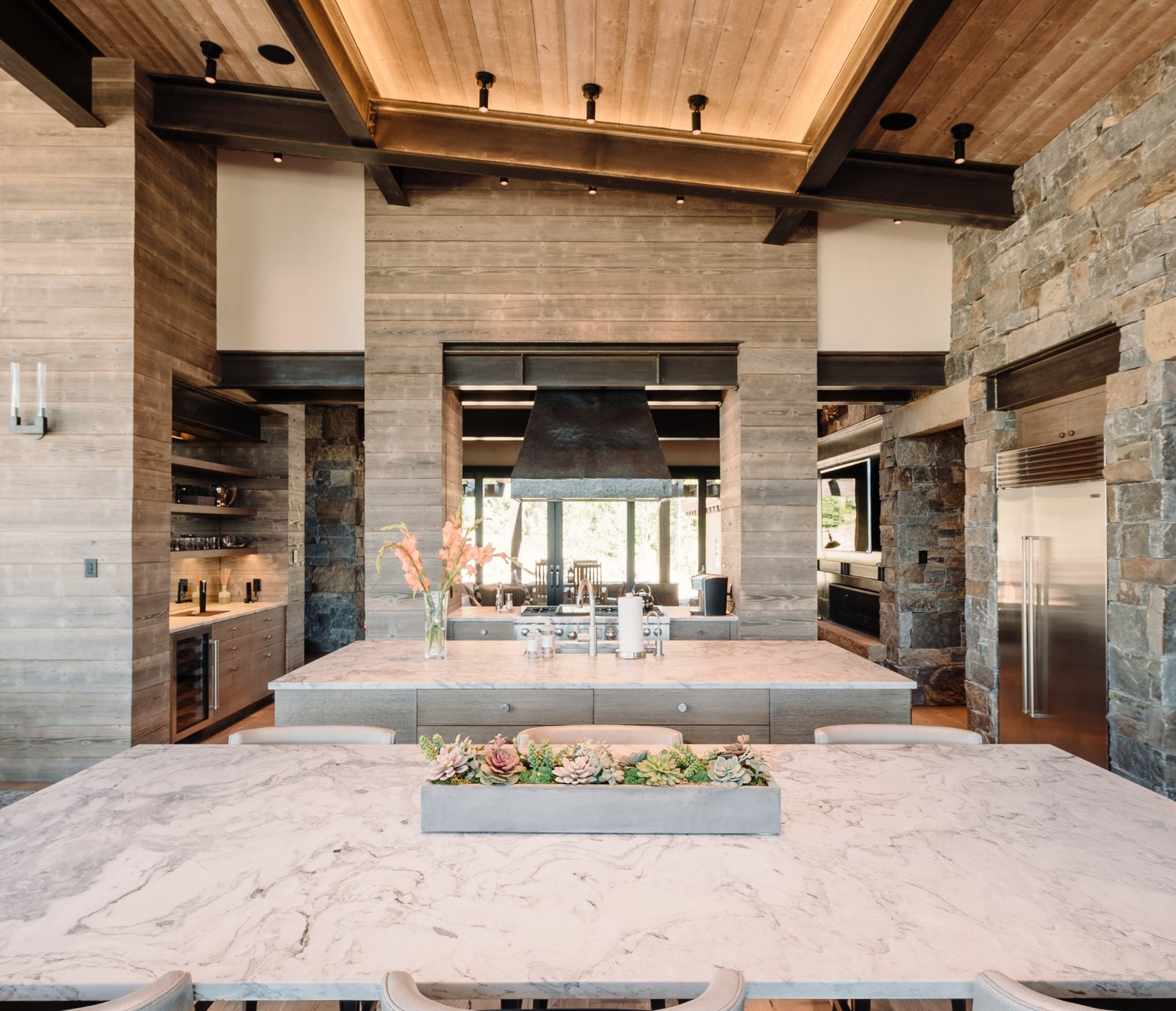 "Kitchen, Refrigerator, Beverage Center, Ceiling, Range, Range Hood, and Medium Hardwood ""We wanted it to be a restful environment,"" says interior designer Ashley Sanford. ""Everything has a matte finish so that your eye slides across everything. There aren't harsh elements that distract.""  Best Kitchen Beverage Center Range Ceiling Photos from A Mountain Retreat in Montana Allows One Couple to Live in the View"
