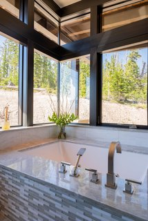 In the master bath, a zero corner window allows the homeowners to soak in views of the wilderness.