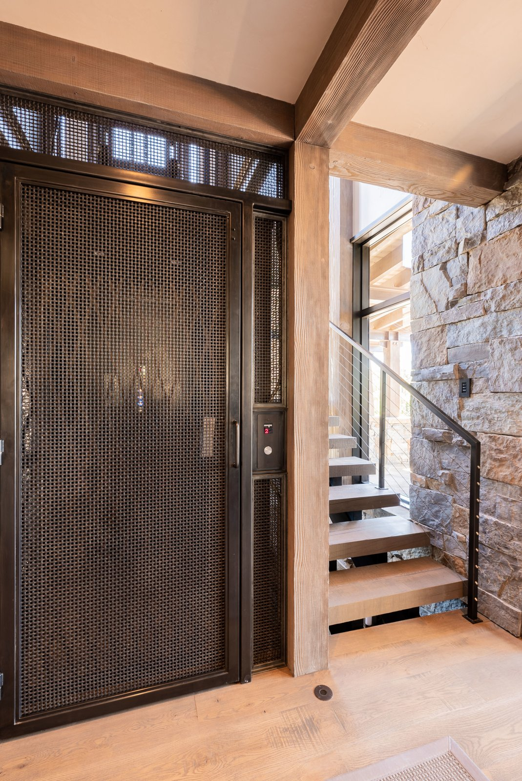Staircase, Metal Railing, and Wood Tread A steel elevator, wrapped by a staircase, anchors the home and descends downstairs to the bunk room.  Photo 10 of 12 in A Mountain Retreat in Montana Allows One Couple to Live in the View
