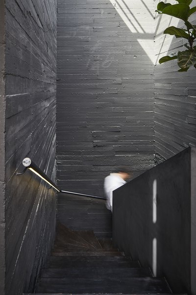 "The walls of the stairwell are made of board-formed concrete painted black. ""Everything in the house is experimental,"" Mehdi says of the atypical dwelling, ""the materials, the layout, the garden, the exterior."""