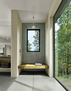In the bathroom, blue-gray Heath Ceramic tiles and Linen Brix tiles by Naoto Fukasawa line the shower.