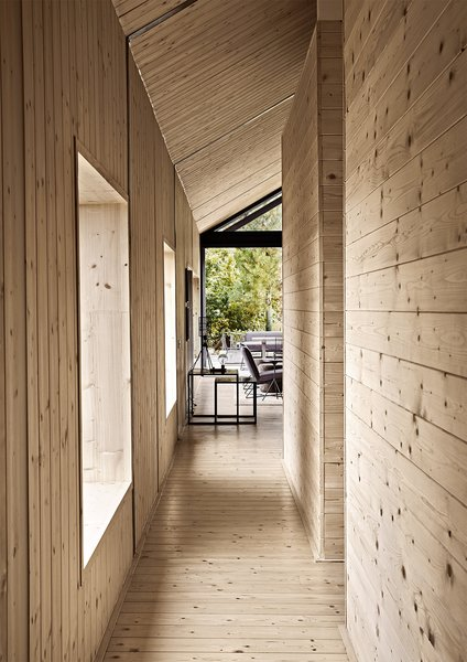 """The interior of the house is completely """"skinned,"""" as Scott puts it, in knotty spruce. A lamp from Weylandts sits  atop nesting tables from  James Mudge Furniture Studio."""