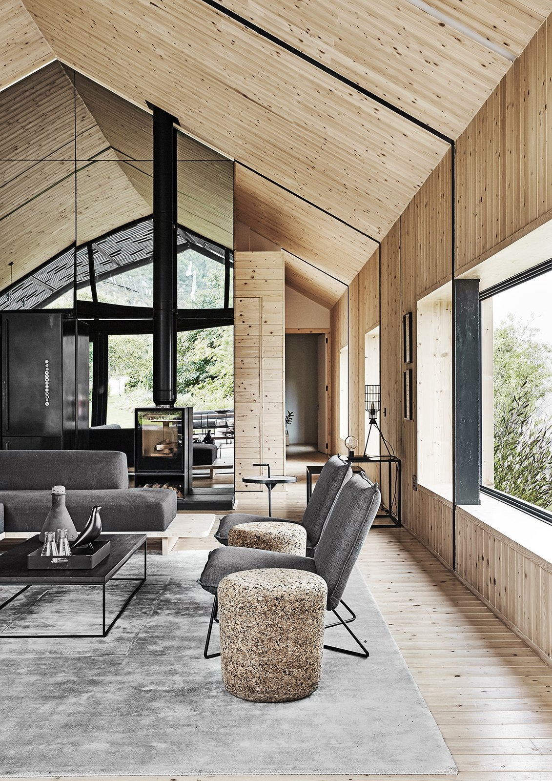 Living, Medium Hardwood, Coffee Tables, End Tables, Two-Sided, Sofa, Chair, and Wood Burning Scott set the windows into deep recesses.  Best Living Sofa Two-Sided Photos from A Hotelier Realizes a Modern Barn for His Family's Retreat in South Africa
