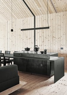 """The dining table is an extension of the kitchen counter, which features a blackened brass surface that """"underpins the industrial aesthetic we were working with,"""" says Scott. The small pendant is from Diesel with Foscarini and  the strip pendant is from Spazio."""