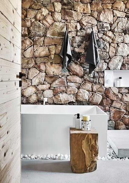 Scott incorporated rough stones excavated on the property into the bathrooms, creating a contrast with the clean lines of the rest of the house. The tub is custom.