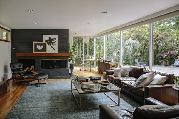 The living room is furnished with an Eames lounge and ottoman and a Line credenza by Nathan Yong. The fireplace, also painted by the last owner, is Wrought Iron by Benjamin Moore.