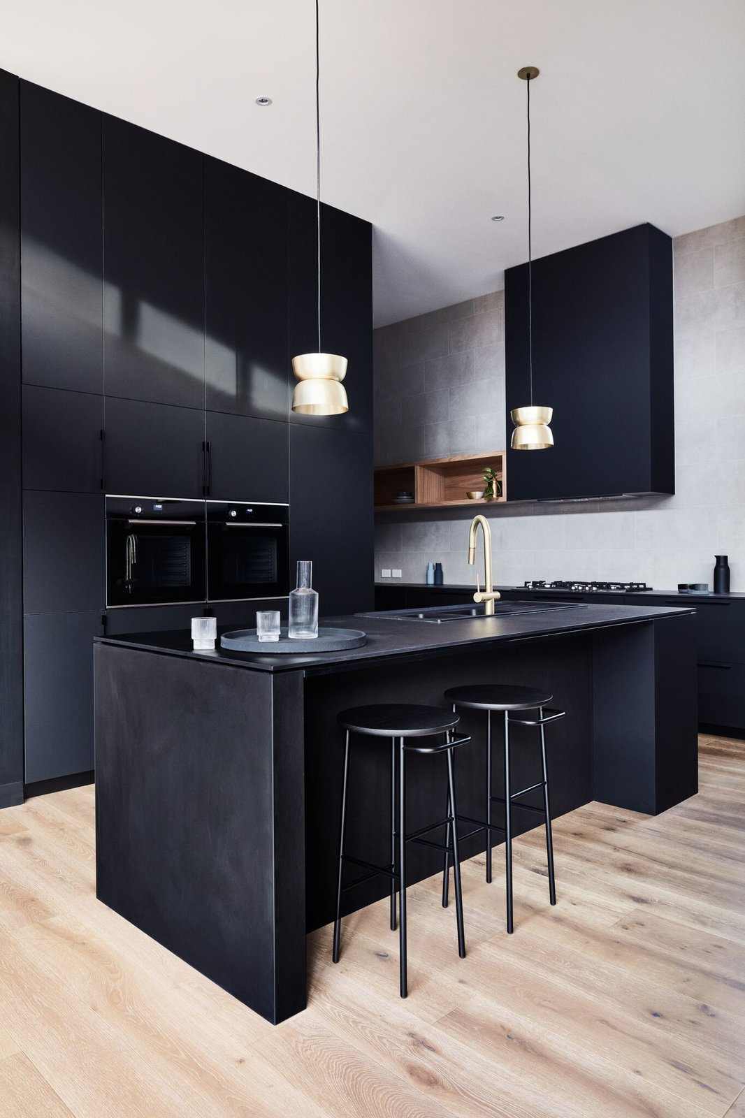Kitchen, Drop In Sink, Wall Oven, Pendant Lighting, Medium Hardwood Floor, Recessed Lighting, and Cooktops The kitchen appliances selected for this project were from De Dietrich.  Photo 8 of 16 in A Striking Courtyard Awaits Behind These Bluestone Walls