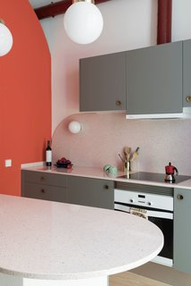 The kitchen cabinets are finished in a warm gray, and are fitted with vintage, brass concave handles.