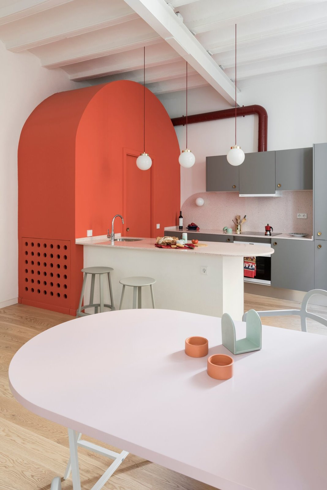 Dining Room, Bar, Pendant Lighting, Light Hardwood Floor, Stools, and Wall Lighting Revolver stools by HAY complement the home's colorful interior.  Photo 16 of 26 in Before & After: An Ancient Barcelona Apartment Gets a Colorful, Chic Makeover