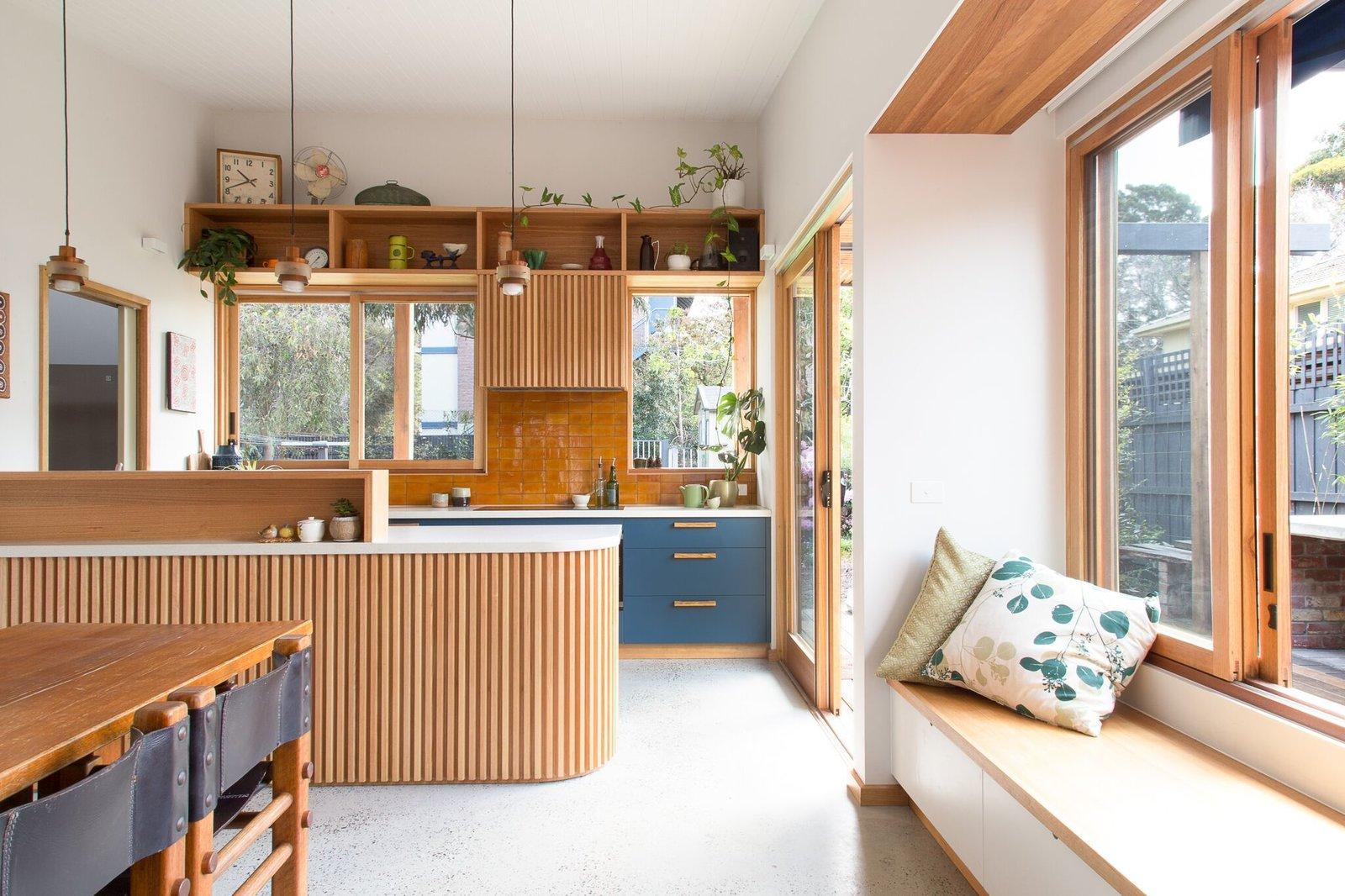 Dining Room, Chair, Table, Pendant Lighting, Concrete Floor, and Storage A connected dining area and kitchen allows for an open, airy feeling.  Photo 7 of 15 in A Cramped Bungalow Is Reborn as an Eco-Minded Abode For Two Gardeners