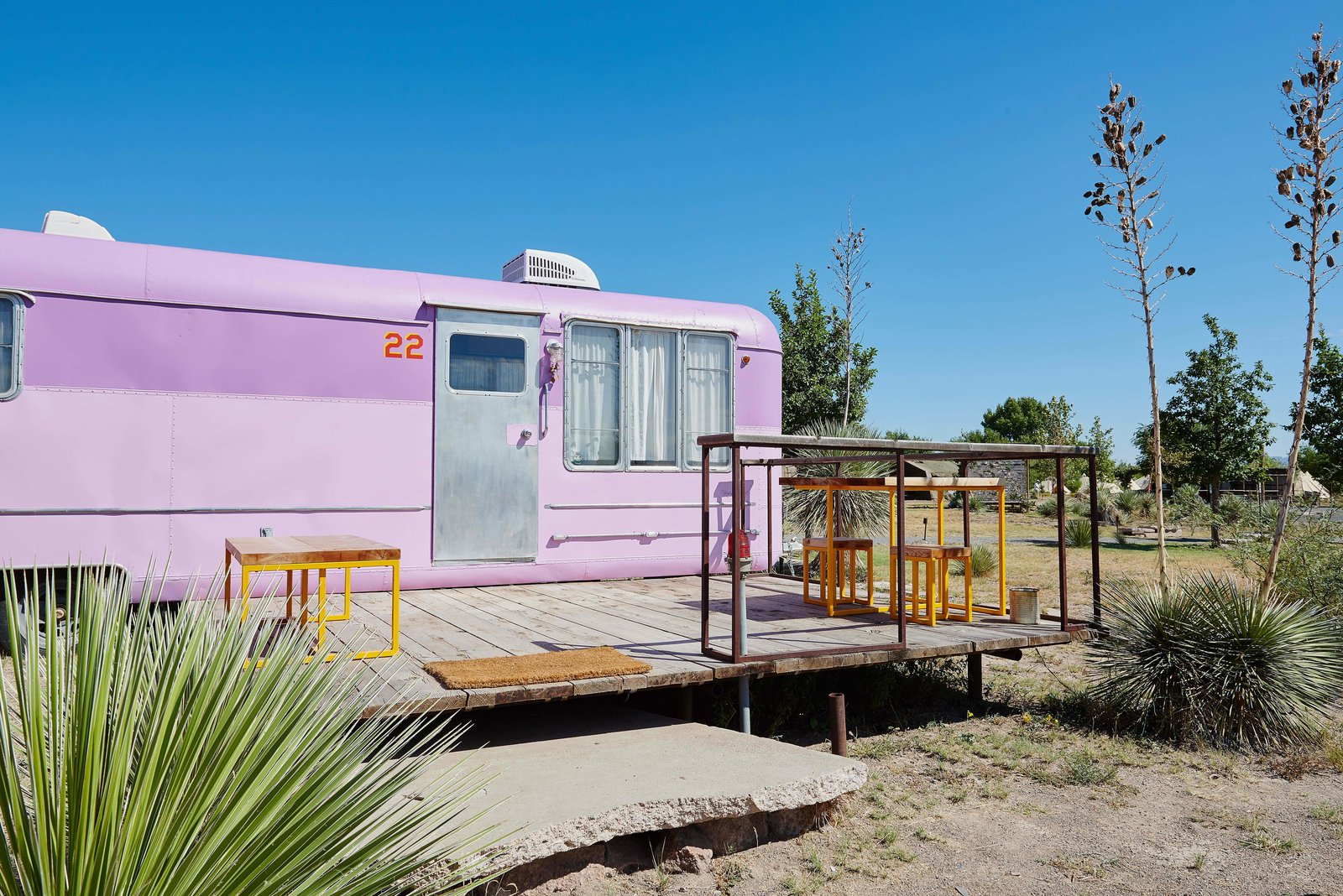 Outdoor, Front Yard, Desert, Small Patio, Porch, Deck, Wood Patio, Porch, Deck, Decking Patio, Porch, Deck, Boulders, and Shrubs The Vagabond Trailer at El Cosmico features a pink exterior and restored, marine-varnished birch interiors.  Photos from Journey by Design: Marfa, Texas