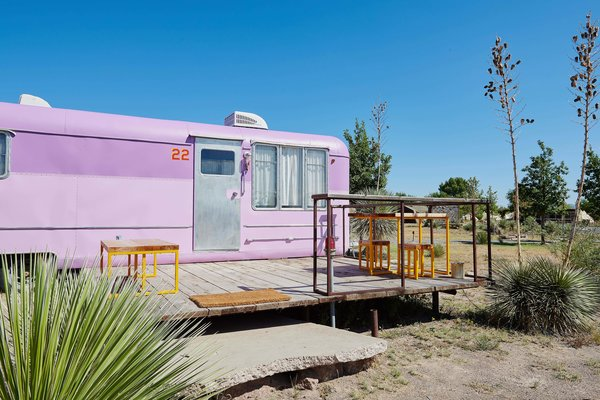 Outdoor, Front Yard, Desert, Small Patio, Porch, Deck, Wood Patio, Porch, Deck, Decking Patio, Porch, Deck, Boulders, and Shrubs The Vagabond Trailer at El Cosmico features a pink exterior and restored, marine-varnished birch interiors.  Best Photos from Journey by Design: Marfa, Texas