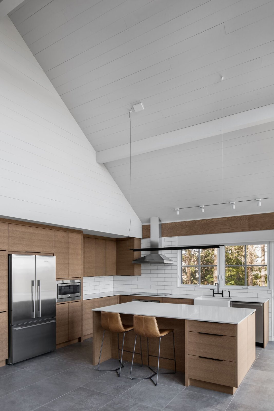 Kitchen, Pendant, Cooktops, Refrigerator, Range Hood, Wood, Vessel, Dishwasher, Wall Oven, Track, and Subway Tile The homey, open kitchen is fully equipped for cooking family meals together.  Best Kitchen Subway Tile Wall Oven Wood Photos from A 1960s Canadian Ski House Is Rebuilt Into a Gorgeous Abode