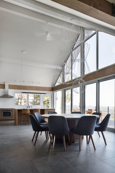 The dining room suspension light is a custom design by Robert Franco. The dining chairs are by West Elm.