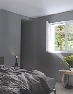 A bedroom window frames forest views.