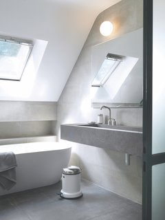 A skylight allows natural light to flow over the freestanding tub. The taps, soap dispenser, and pedal bin are by Vipp.