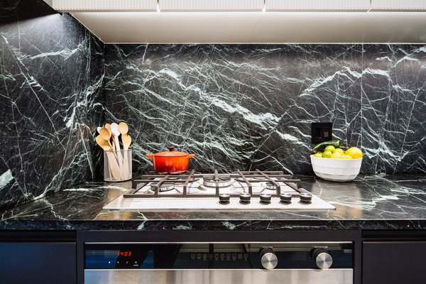 The dramatic, veiny dark-green marble countertop and matching backsplash of this restored Ludwig Mies van der Rohe townhouse in Detroit aren't original, but the stone matches a variety that Mies used in other projects around the same time.