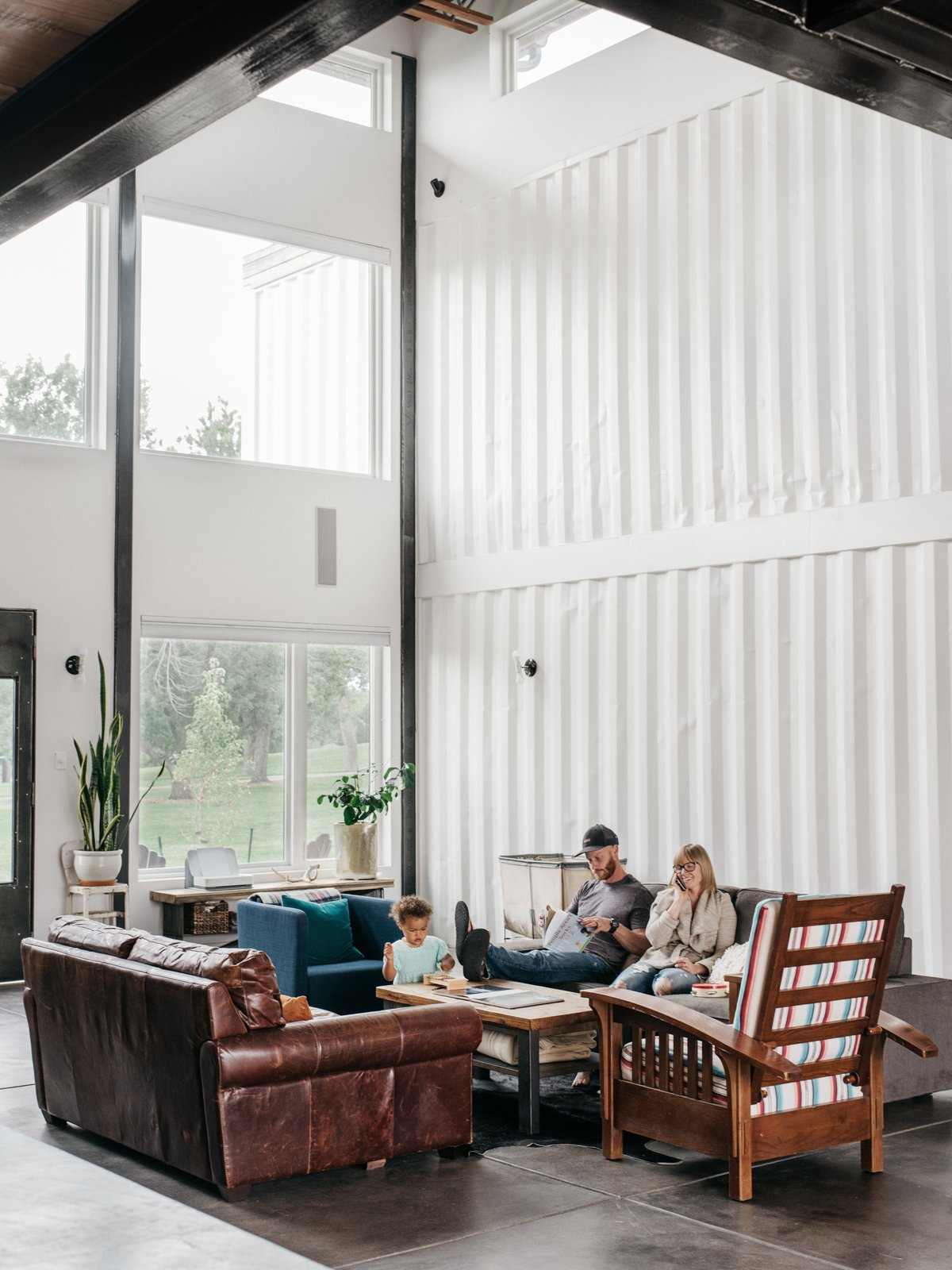 Living Room, Sofa, Concrete Floor, and Coffee Tables The Fosters unwind in the soaring, 960-square-foot great room. The family wanted plenty of space for hosting friends and events, as well as lots of bedrooms so they can rent the house to groups on Airbnb if they like.  Photo 2 of 13 in A Colorado Firefighter Built His Own Shipping Container Home, and Found a New Calling Along the Way